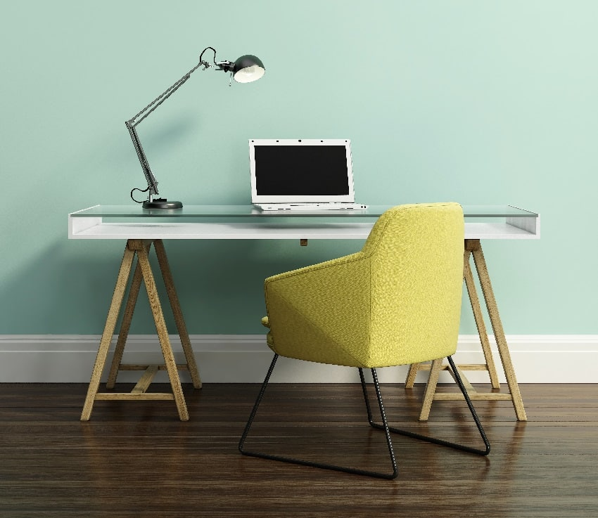 contemporary home office with yellow armchair desk laptop and lamp on it