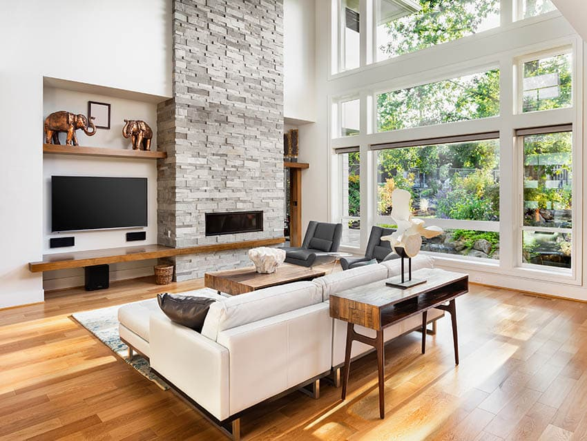 Contemporary living room with douglas fir flooring stacked stone fireplace wall of windows