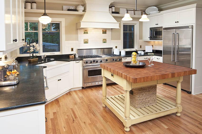 Country kitchen with end grain butcher block island white cabinets black soapstone countertops