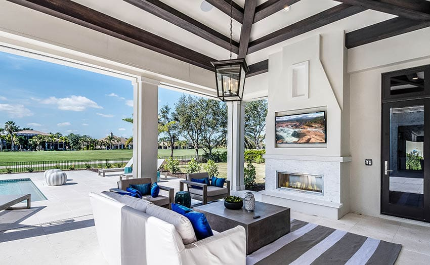 Covered outdoor patio with tv mounted on stucco walls