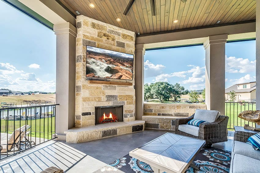 Covered patio with outdoor tv mounted above fireplace
