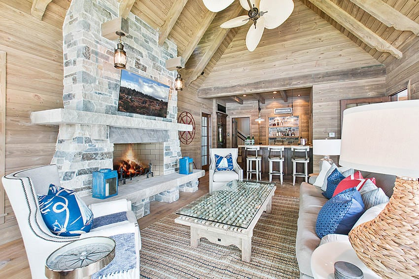 Covered patio with vaulted ceiling hanging outdoor tv on fireplace wall mount