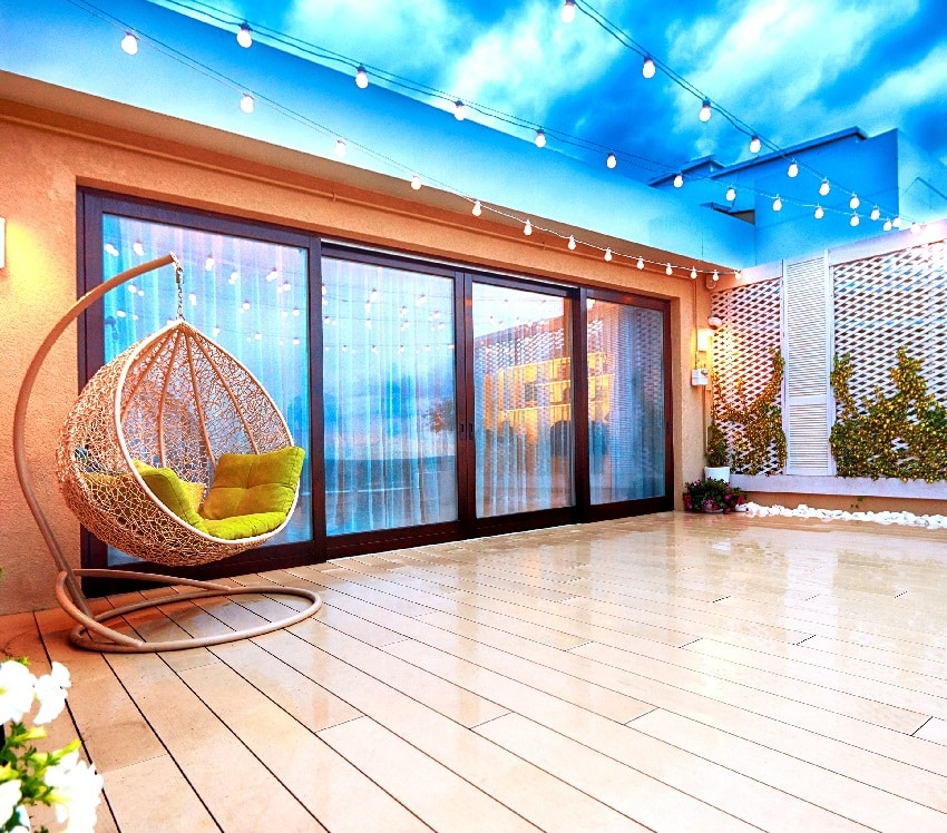 cozy evening wooden deck patio area with sliding doors plants string lights and rattan swing