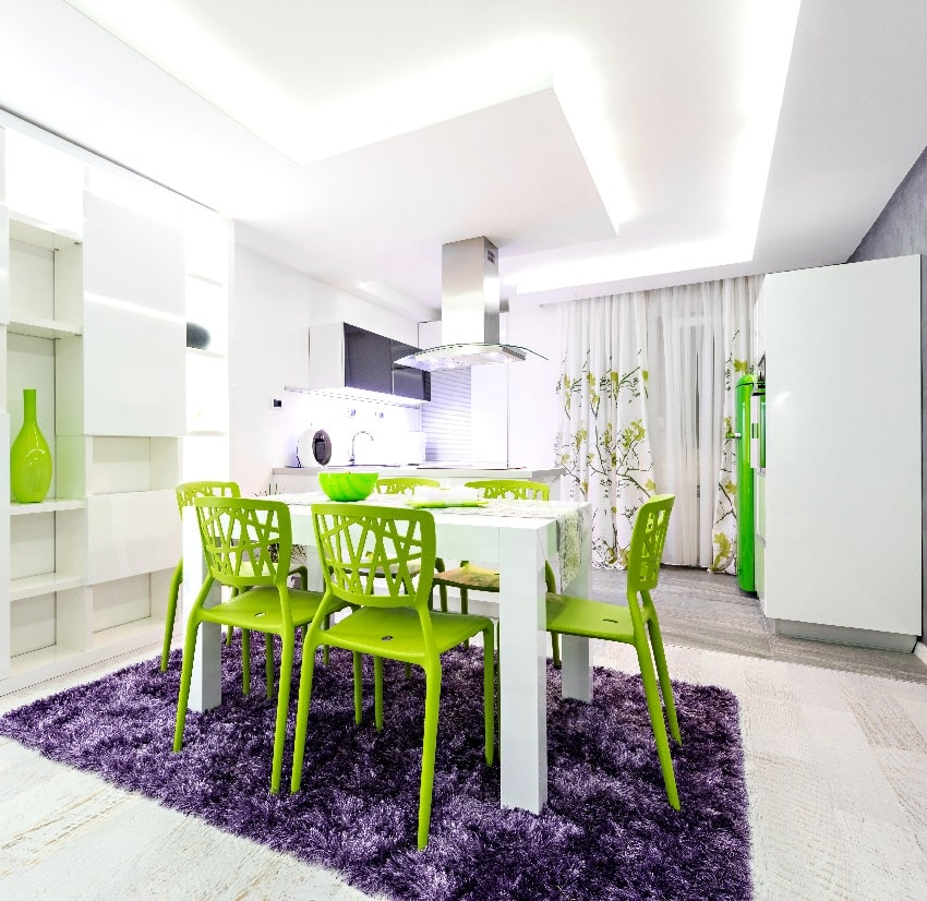 dining area with green chairs white table and purple mat