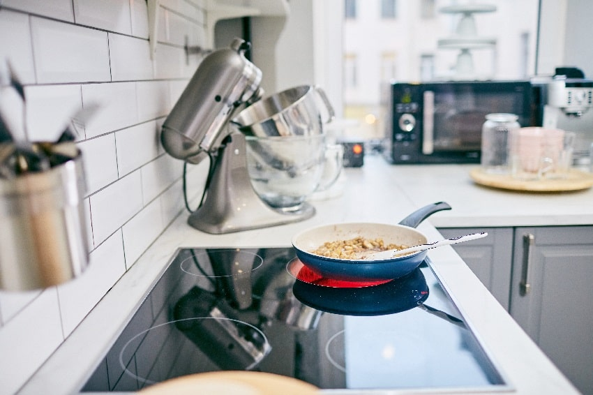 dish being cooked in frying pan on modern induction cooktop in kitchen