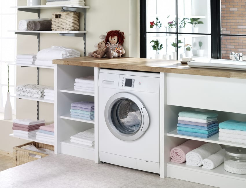 Electric dryer with wood countertop, white cabinets surrounded by clean clothing