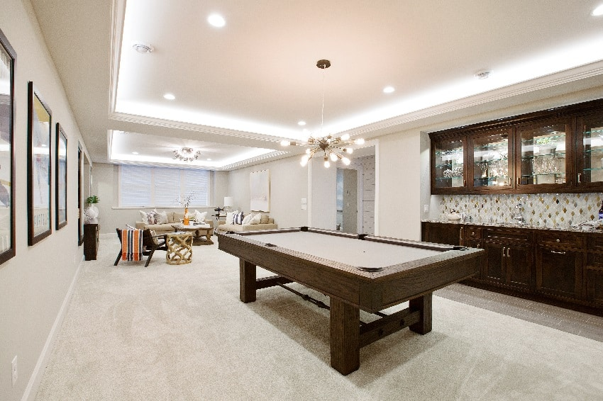elegant basement with white wall paint billiards table with kitchenette nearby
