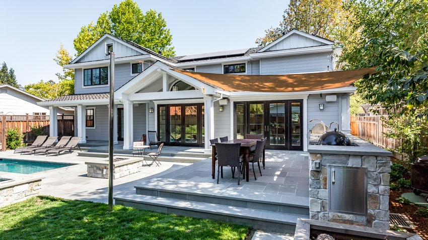 Elevated pool patio with outdoor kitchen grill and canopy cover