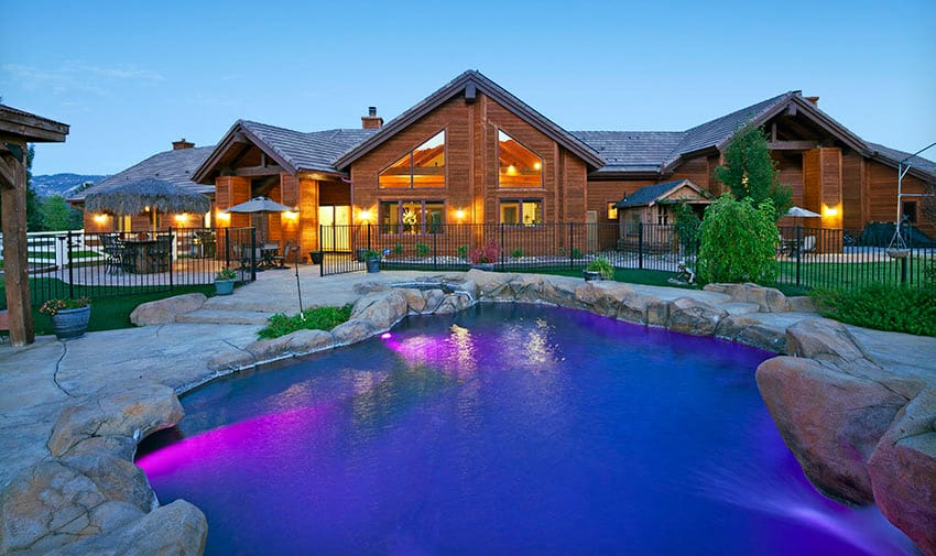 Exterior home with mood lighting and pool