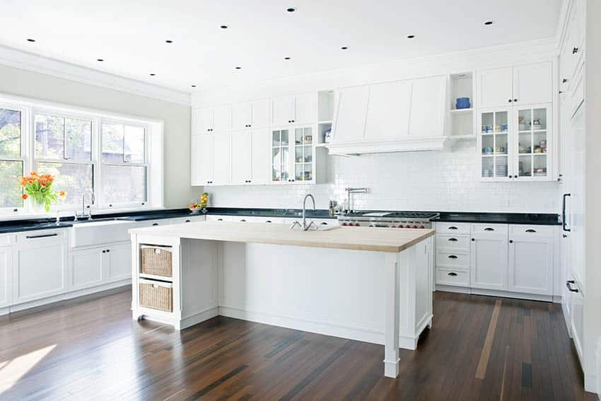 Farmhouse kitchen with wood countertop island white shaker cabinets black granite counters
