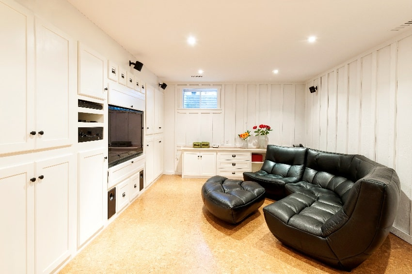 finished basement withcream white wall paint an entertainment center couch and flat screen tv