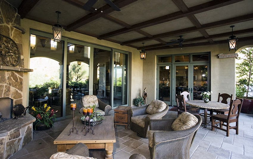 Folding patio door with stone fireplace and outdoor furniture