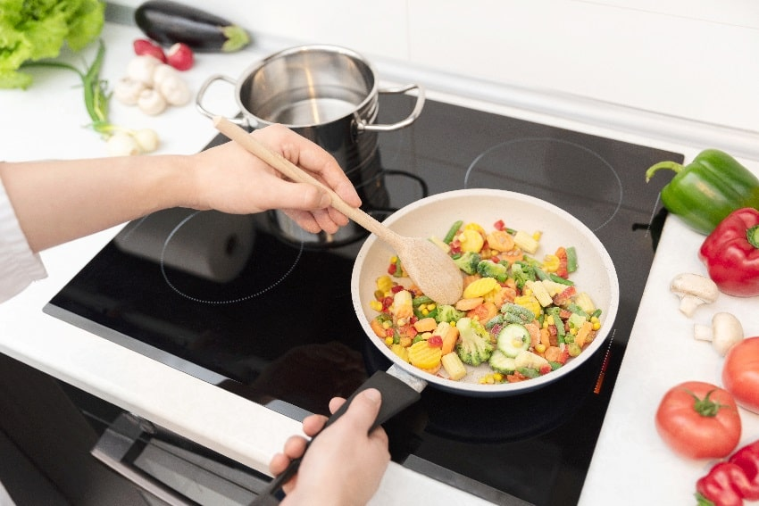 fresh vegetables fried in a pan on a glass ceramic cooktop with some vegetables and herbs around the white kitchen countertop