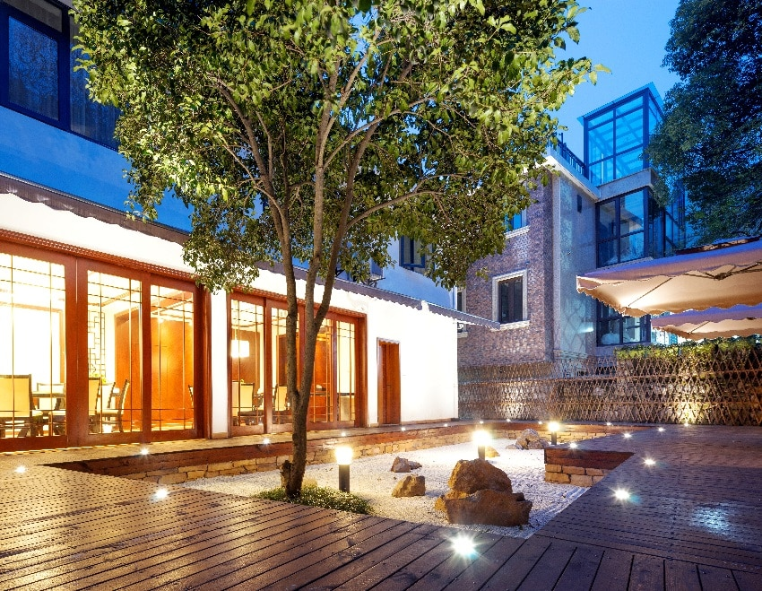 front outdoor deck footpath with recessed lights and tree in the center of modern building at night