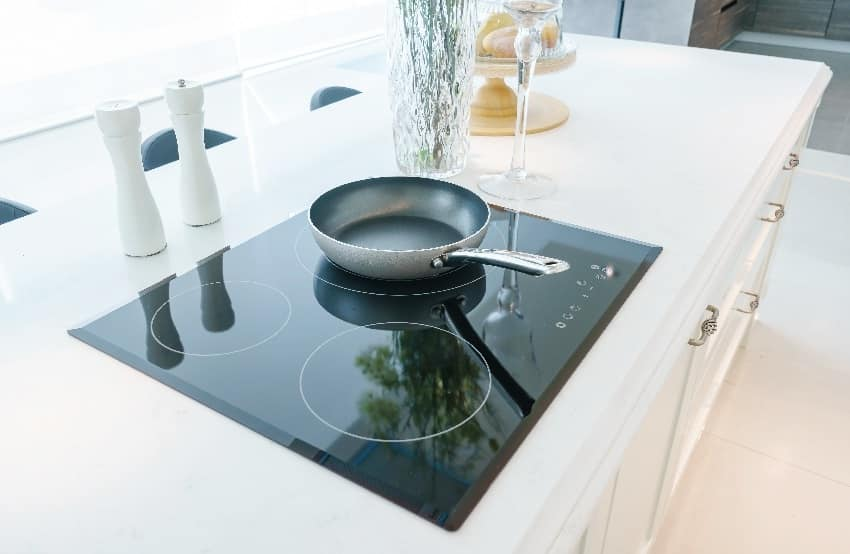 Frying pan on modern black induction cooktop in white kitchen interior