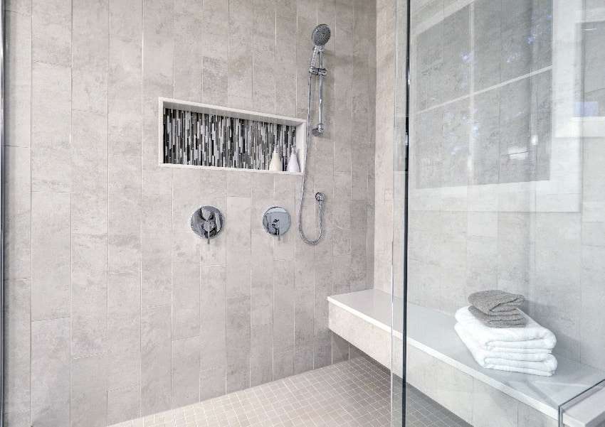 glass walk in shower with floating bench gray subway tiled surround accented with mosaic tile strip in wall