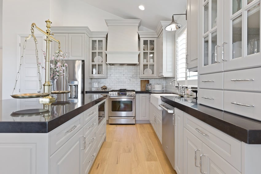 gray kitchen with white cabinets and black granite countertop