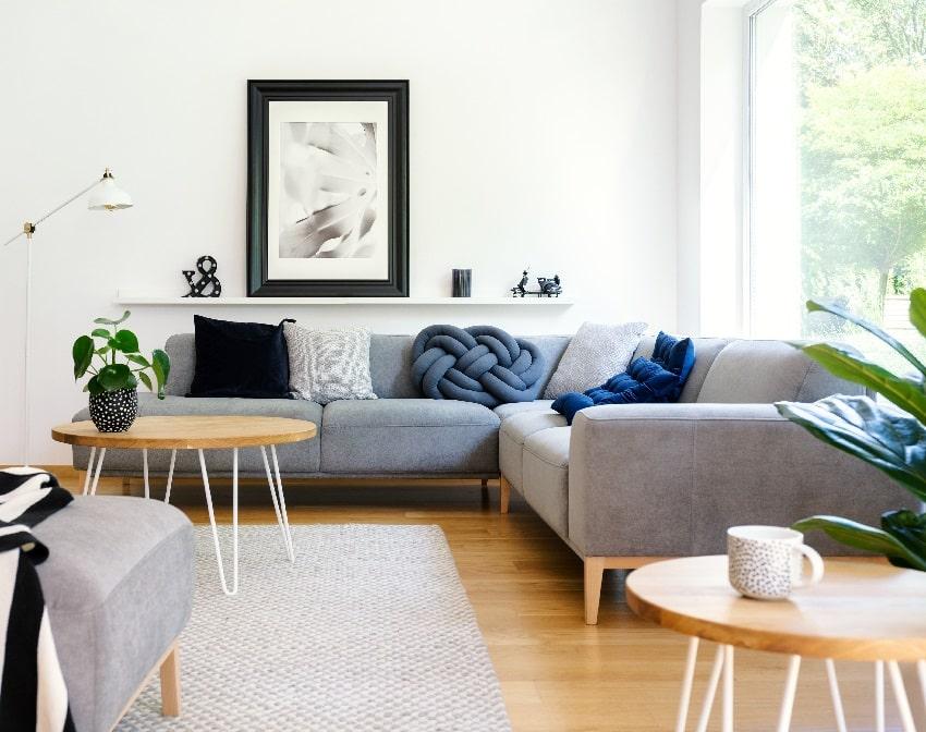 Sofá seccional gris de microfibra en la moderna sala de estar con piso de madera