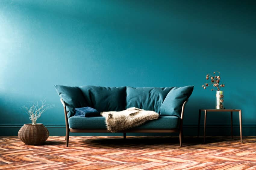 Green fabric sofa in front of wall and wood floor