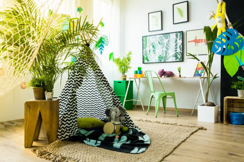 Green playroom with tent chair and frames on wall
