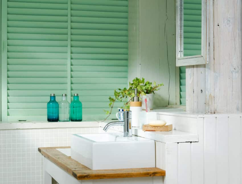 Green wooden bathroom shutters near a white sink