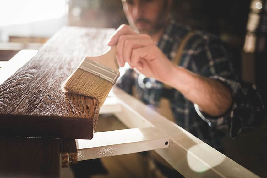 Guy applying varnish to furnitures
