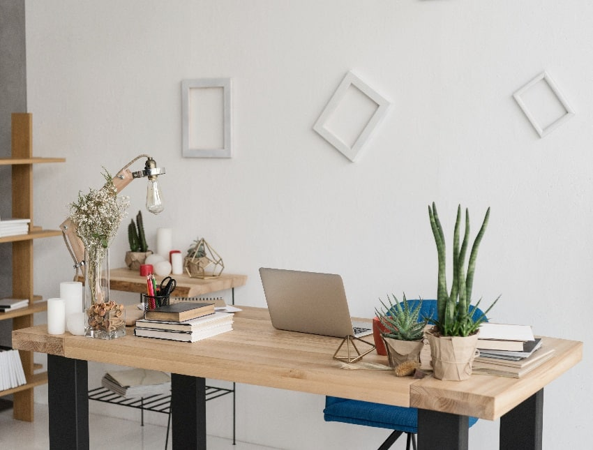 home office with white background wall decors office table with laptop books candles and office supplies
