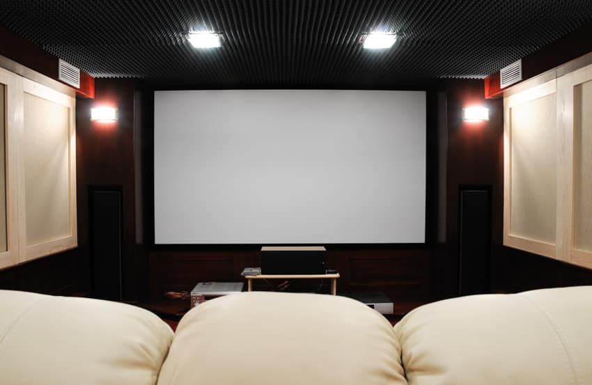 Home theater with black ceiling and white sofa style chairs