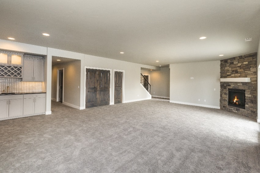 huge open basement room in cream white wall paint and carpet flooring