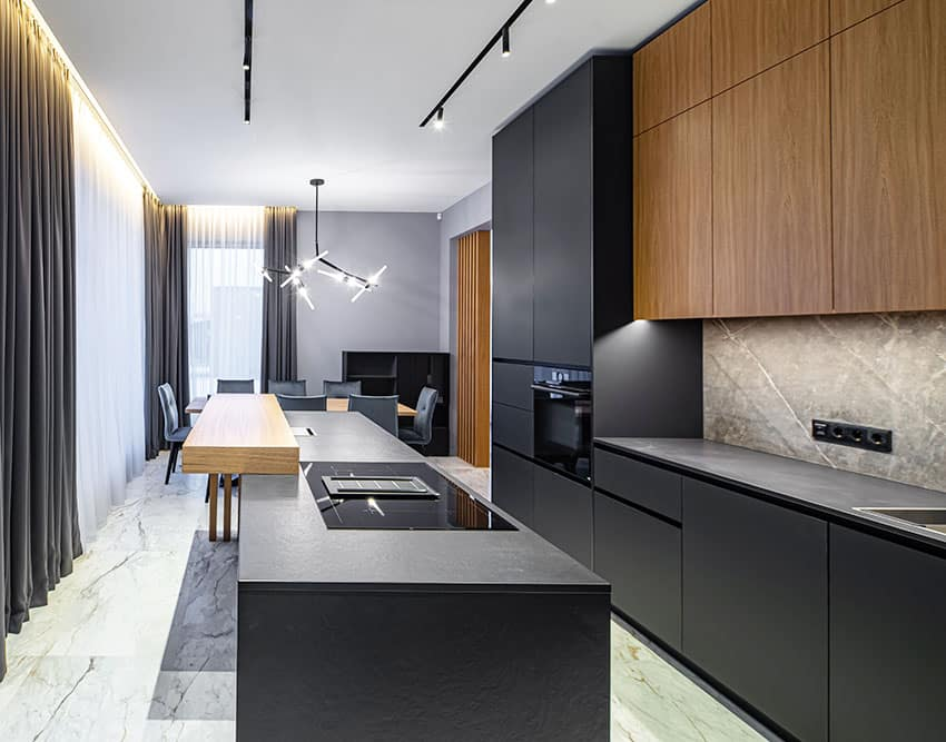 Kitchen with black cabinets, dark curtains, hanging lights, dining table and center island