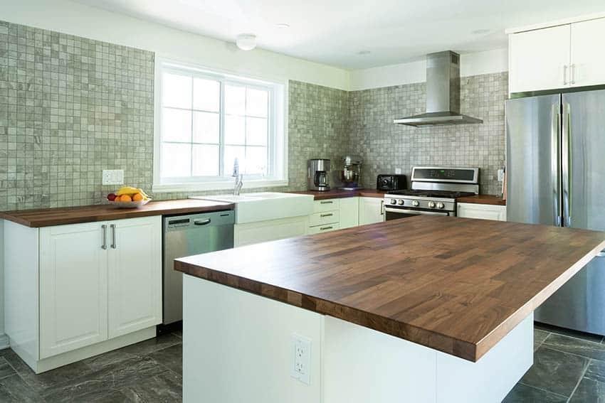Kitchen with butcher block wood countertops white cabinets mosaic tile full wall backsplash