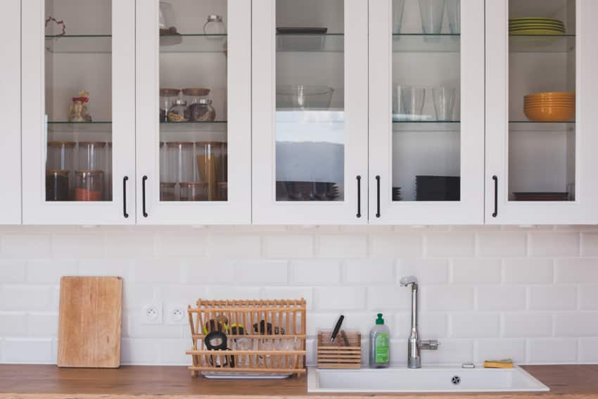 Kitchen with glass door cabinets sink and kitchenware