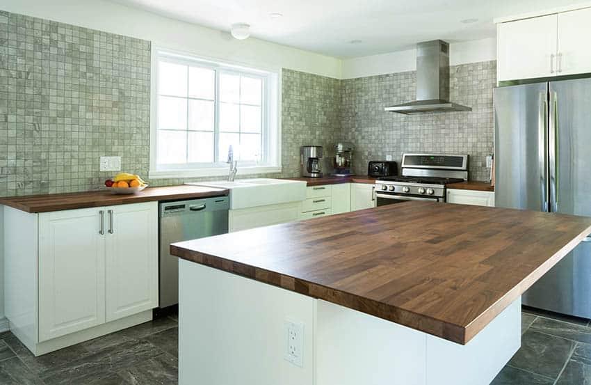 Kitchen with wood countertops island white cabinets mosaic tile backsplash