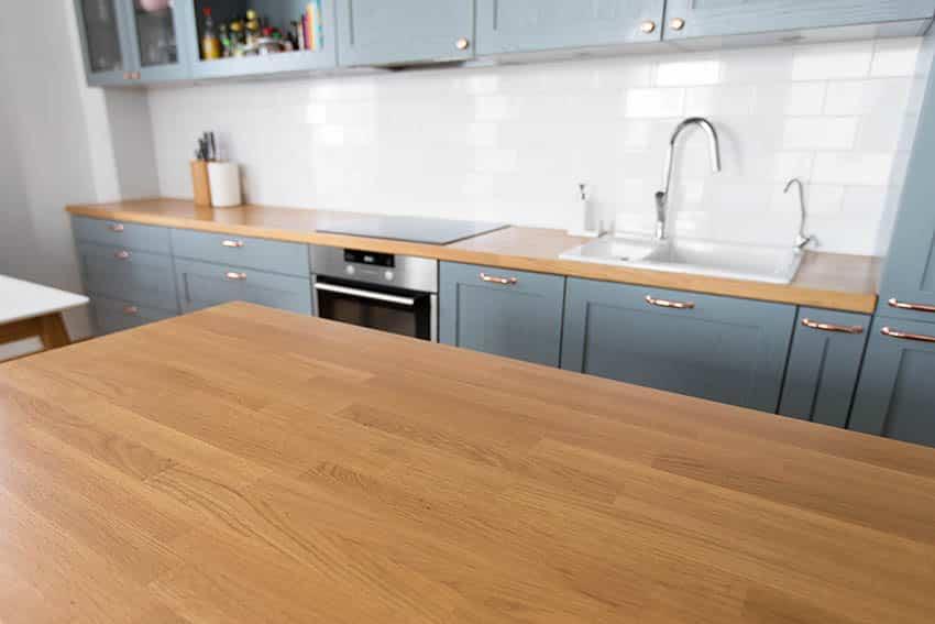 Kitchen with wood countertops, light gray blue cabinets white tile backsplash