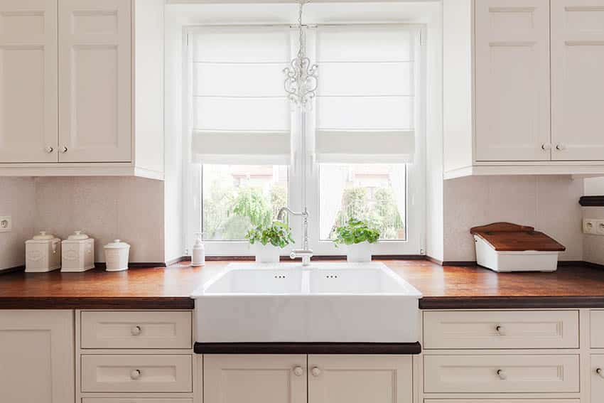 Kitchen with wood countertops white cabinetry farmhouse sink