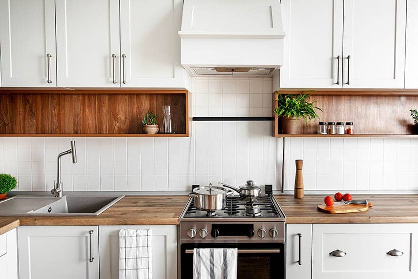 Kitchen with wood countertops white cabinets square tile backsplash wood lined open shelving