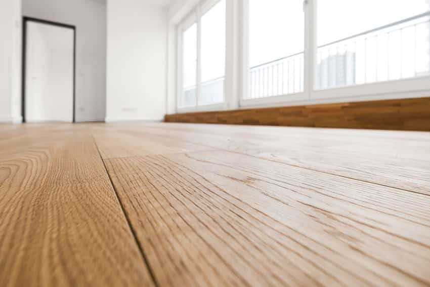 Laminate flooring in an empty room with large windows