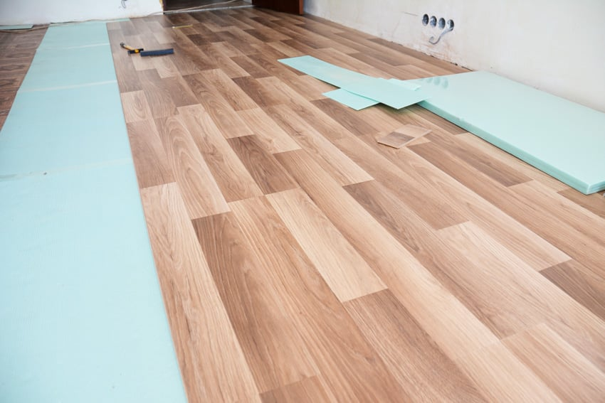 Laminate flooring with attached underlayment construction