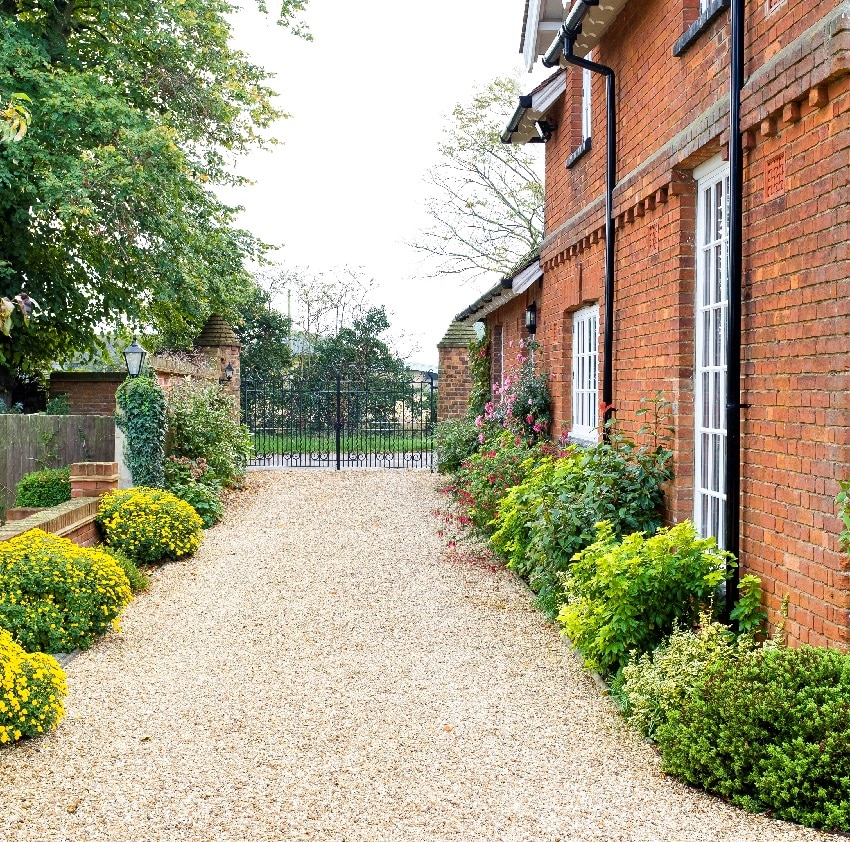 country mansion house with wrought iron gates and gravel drive