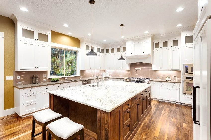 large kitchen interior with wooden island sink white cabinets pendant lights and hardwood floors