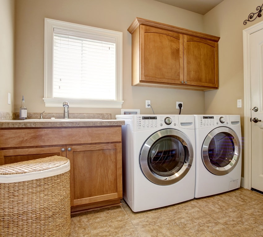 laundry room with cream white wall paint washer dryer and wooden cabinets