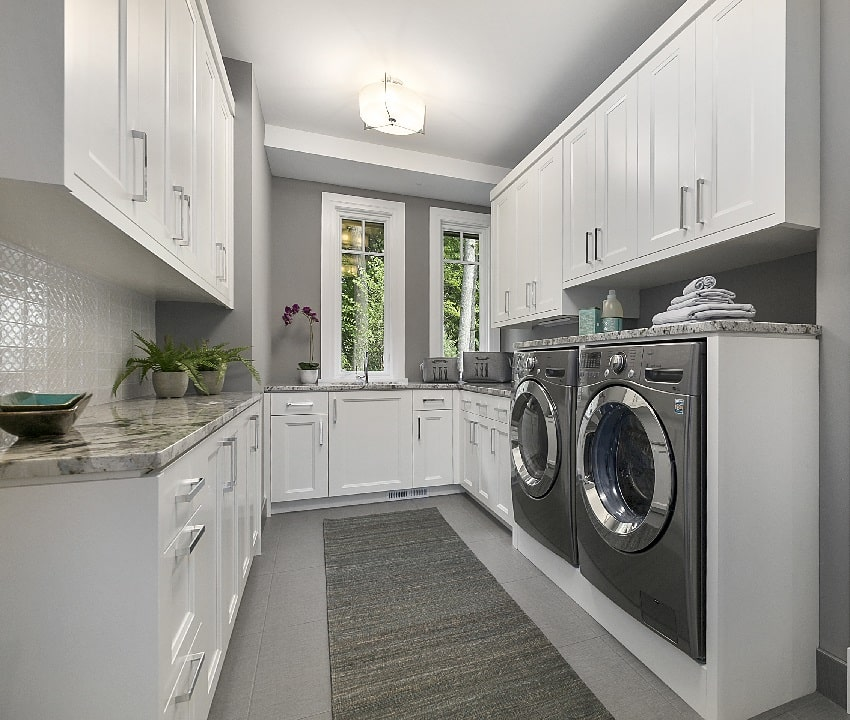 laundry room with gray wall paint and white storage cabinets