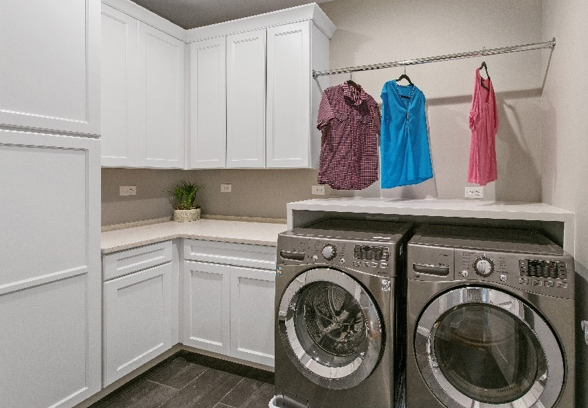 laundry room with white storage cabinets and hanged clothes on top of washer dryer