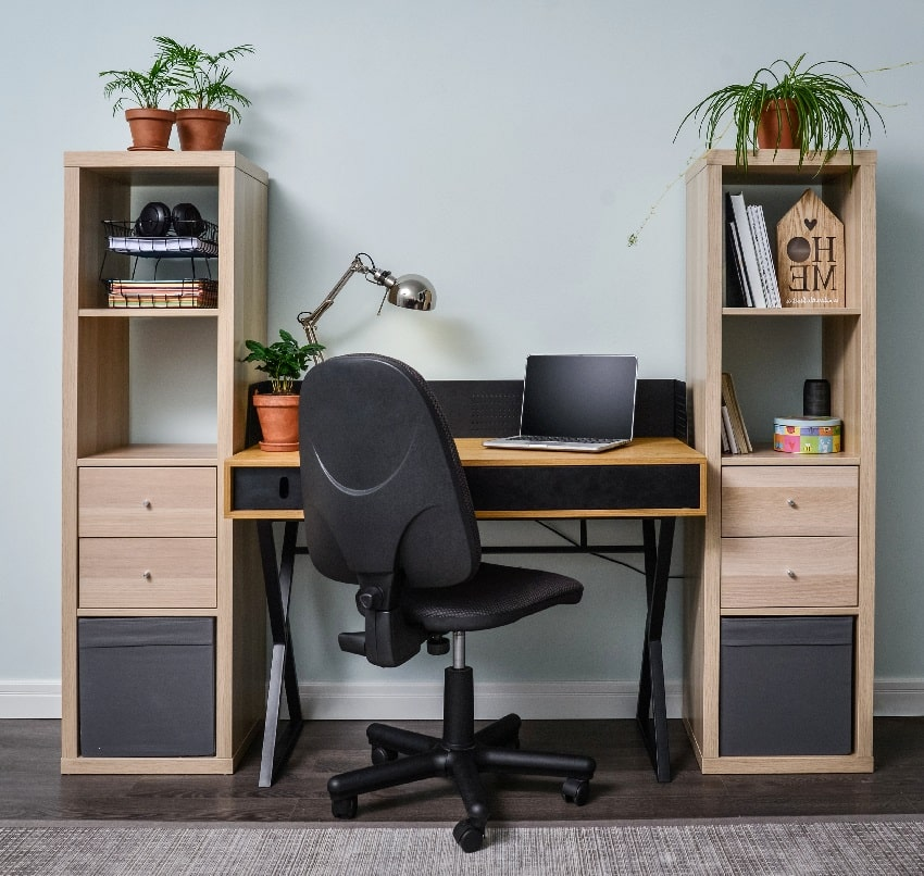 light cozy home office room with wooden bookcases, working desk laptop and black office chair