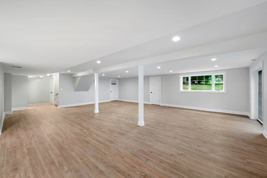 ight grey spacious basement area with wood flooring
