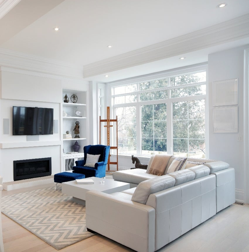 living room with hardwood floor and rug furnished with beige sofas and white coffee table and tv on wall