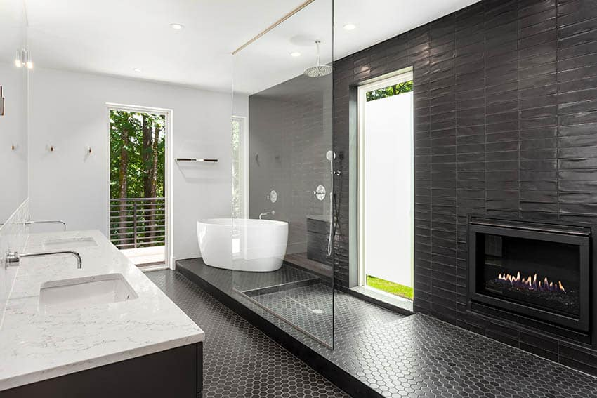 Luxury bathroom with black hexagon mosaic floor tile shower freestanding tub marble countertops gas fireplace