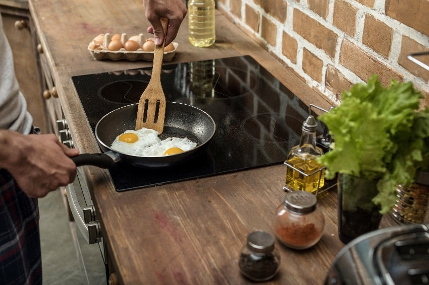 man cooking eggs in a frying pan on a ceramic cooktop for breakfast in wooden kitchen counter