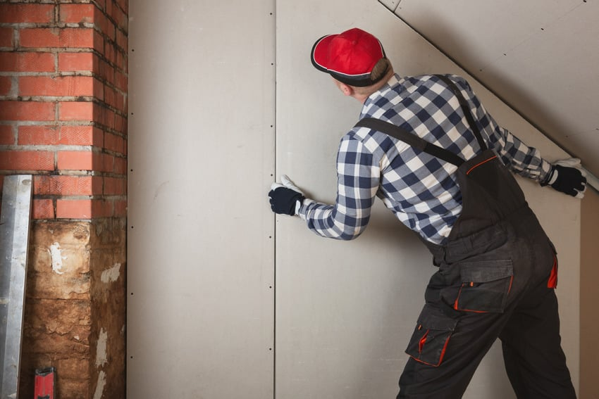 Man installing drywall panel for room construction