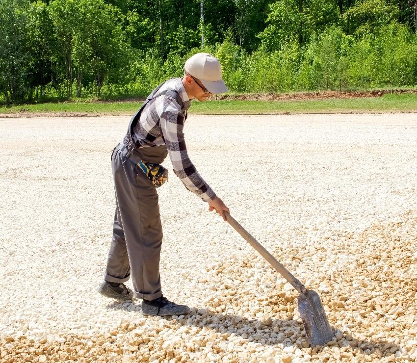 man levels gravel with a shovel